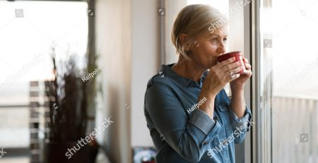 stock-photo-senior-woman-at-the-window-holding-a-cup-of-coffee-572357359